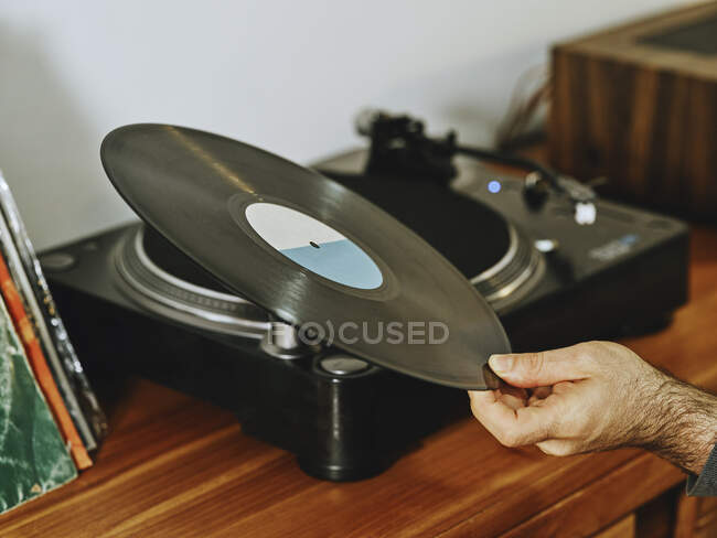 Cropped unrecognizable person setting turntable and enjoying songs on retro vinyl disc while chilling at home — Stock Photo