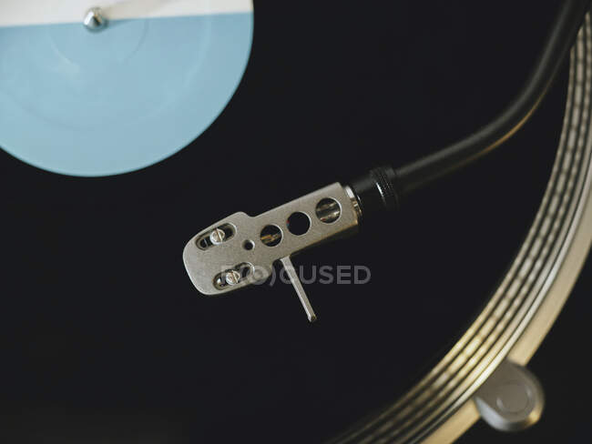 From above close up of contemporary vinyl record player with retro disc placed on wooden table in living room — Stock Photo