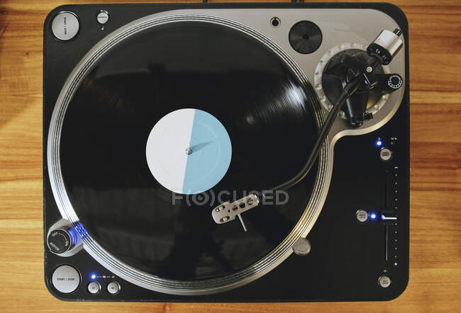 Top view of contemporary vinyl record player with retro disc placed on wooden table in living room — Stock Photo