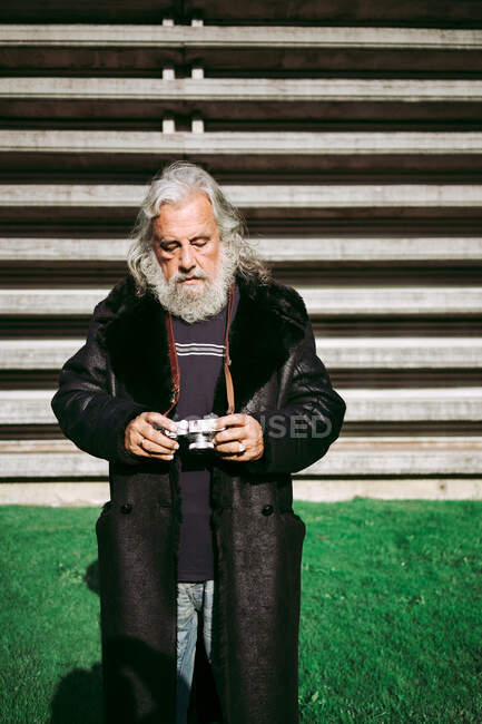 Elderly man in trendy clothes standing in city near urban building and taking pictures on retro photo camera — Stock Photo