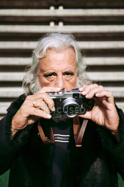 Homem idoso olhando para a câmera em roupas da moda em pé na cidade perto do edifício urbano e tirando fotos na câmera de fotos retro — Fotografia de Stock