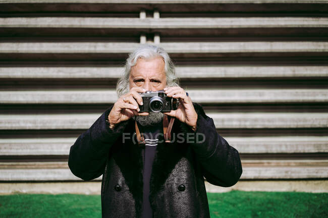 Elderly man looking at camera in trendy clothes standing in city near urban building and taking pictures on retro photo camera — Stock Photo