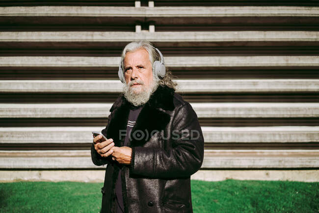 Serious male hipster with long gray hair standing looking away in street on sunny day and enjoying songs in wireless headphones while using smartphone — Stock Photo