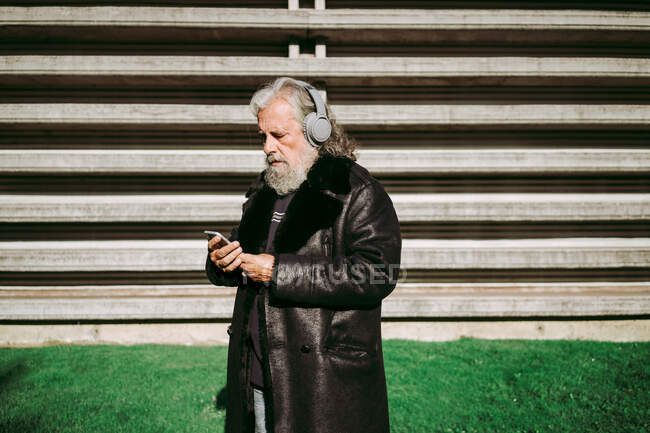 Serious male hipster with long gray hair standing in street on sunny day and enjoying songs in wireless headphones while using smartphone — Stock Photo