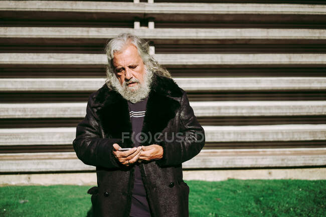 Serious male hipster with long gray hair standing in the street while using mobile phone — Stock Photo