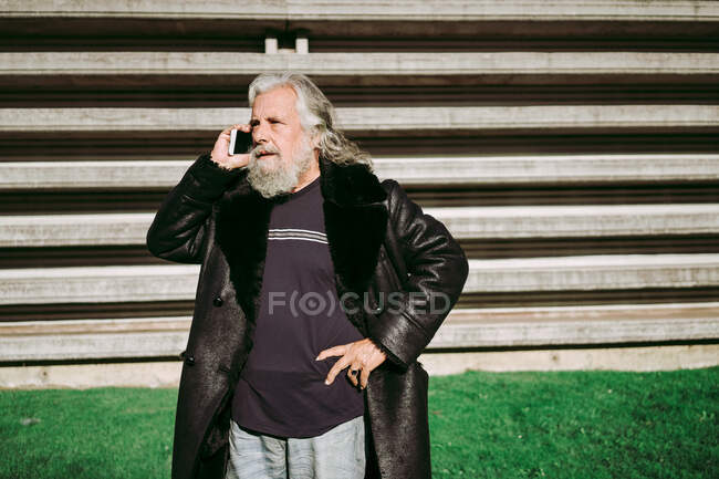Serious male hipster with long gray hair standing in the street while looking away using mobile phone — Stock Photo