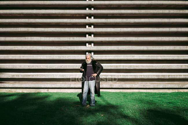 Grave hipster maschile con lunghi capelli grigi in piedi in strada nella giornata di sole e godendo di canzoni in cuffie wireless durante l'utilizzo di smartphone — Foto stock