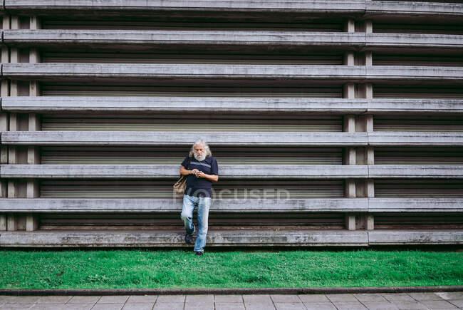Ein älterer männlicher Tourist in Freizeitkleidung steht mit Rucksack in der Nähe eines Steingebäudes und surft auf seinem Handy, während er Informationen über die Stadt sucht — Stockfoto