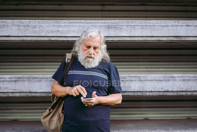 Senior male tourist in casual wear standing with backpack near stone building and browsing cellphone while searching information about city — Stock Photo