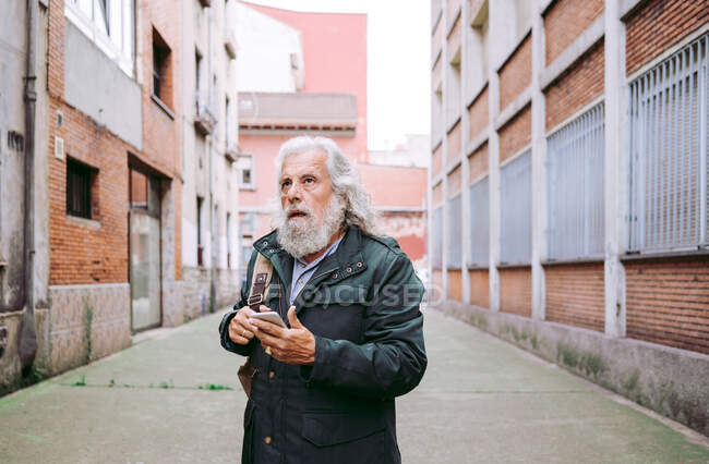 Senior male with long gray hair looking away using mobile phone while walking on the street surrounded by shabby buildings — Stock Photo