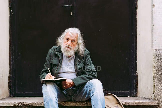 Thoughtful senior male tourist in casual wear sitting with backpack on stone step of shabby building and writing thoughts about vacation in notebook — Stock Photo