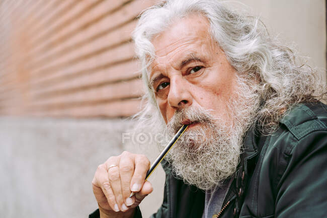 Pensive elderly man with long gray hair sitting on city street and pondering while looking at camera — Stock Photo