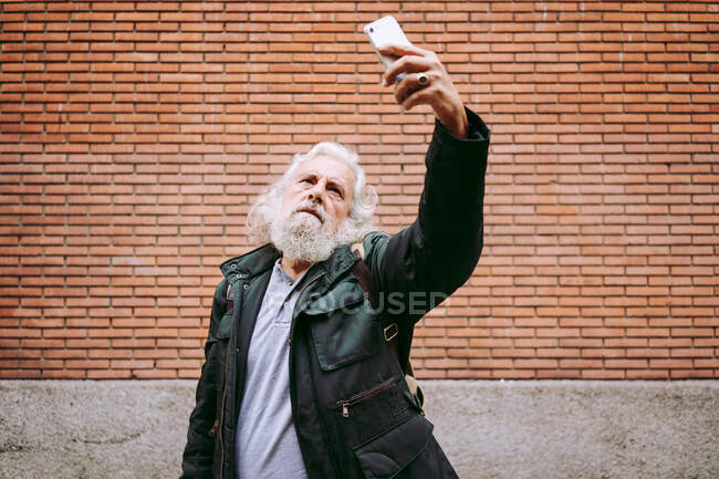 Serious elderly man wearing casual clothes standing on street and taking a selfie on smartphone on background of brick building — Stock Photo