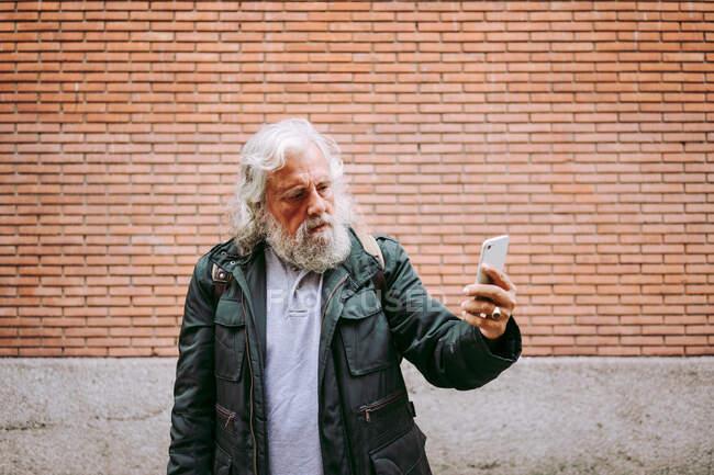 Homem idoso sério vestindo roupas casuais de pé na rua e tirar uma foto no smartphone no fundo do edifício de tijolos — Fotografia de Stock