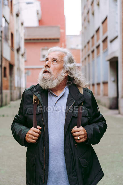 Male tourist in casual jacket walking near shabby buildings while exploring city during holiday looking away — Stock Photo