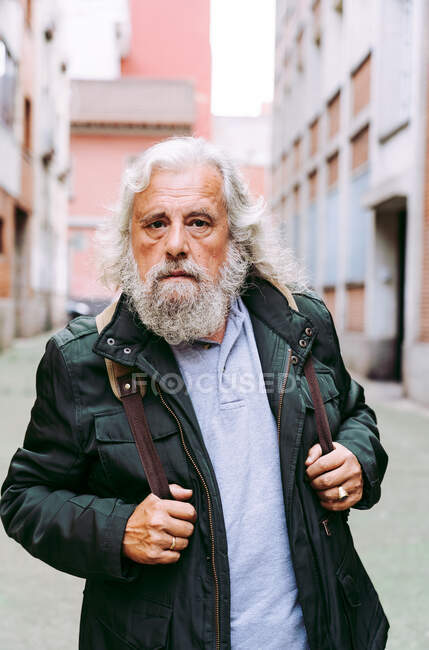 Male tourist in casual jacket walking near shabby buildings while exploring city during holiday looking at camera — Stock Photo