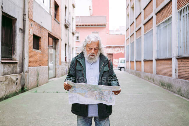 Lost male tourist in casual jacket standing near shabby buildings and orientating on paper map while exploring city during holiday — Stock Photo