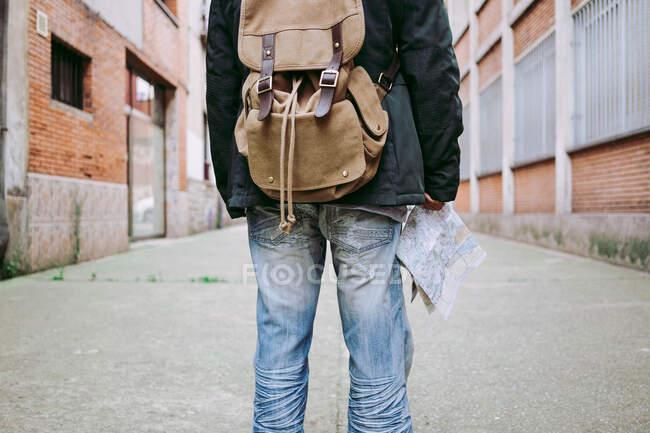 Vista trasera del hombre en equipo casual portando mochila y caminando por la calle con mapa durante el viaje en la ciudad nueva. - foto de stock