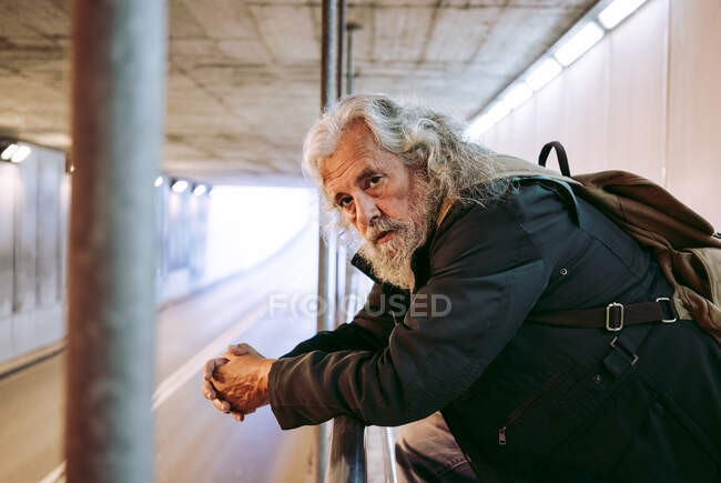 Bearded male tourist with grey hair in outerwear leaning on metal railing construction while standing under bridge with backpack looking at camera — Stock Photo