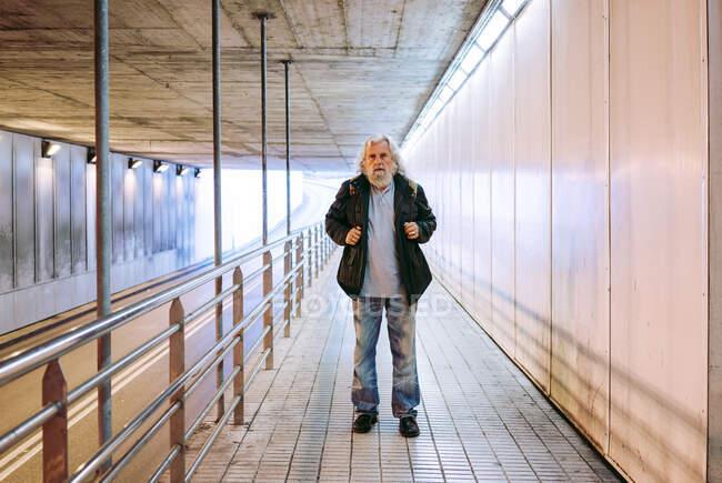 Vista panorámica del maduro peatón masculino caminando desde la distancia hacia la cámara y llevando mochila mientras se entra en el paso subterráneo durante el día. - foto de stock