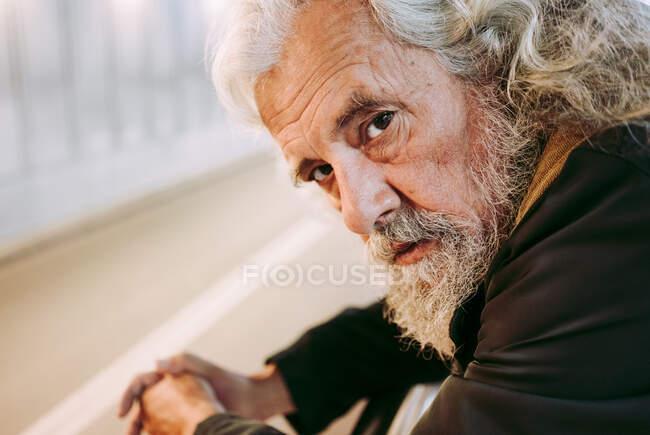Touriste homme barbu avec les cheveux gris dans les vêtements de dessus appuyé sur la construction de garde-corps en métal tout en se tenant sous le pont avec sac à dos regardant la caméra — Photo de stock