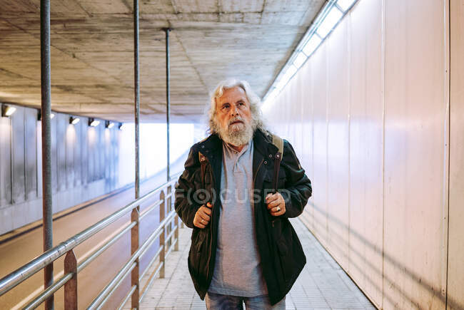 Perspective view of mature male pedestrian walking from distance towards camera and carrying backpack while entering underground crossing at daytime — Stock Photo