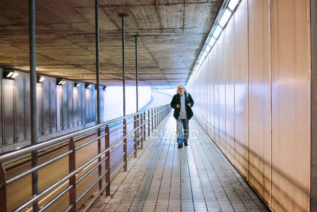 Vue en perspective de piétons mâles matures marchant de loin vers la caméra et portant un sac à dos en entrant dans un passage souterrain le jour — Photo de stock