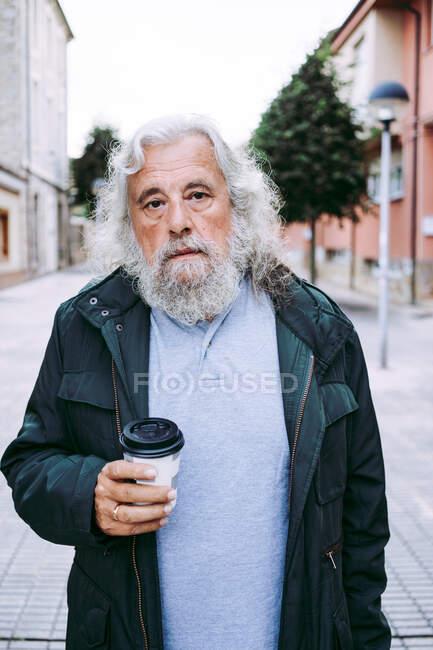 Hombre mayor con pelo gris largo caminar con bebidas calientes para salir a la calle rodeado de edificios poco profundos en la calle mirando a la cámara. - foto de stock