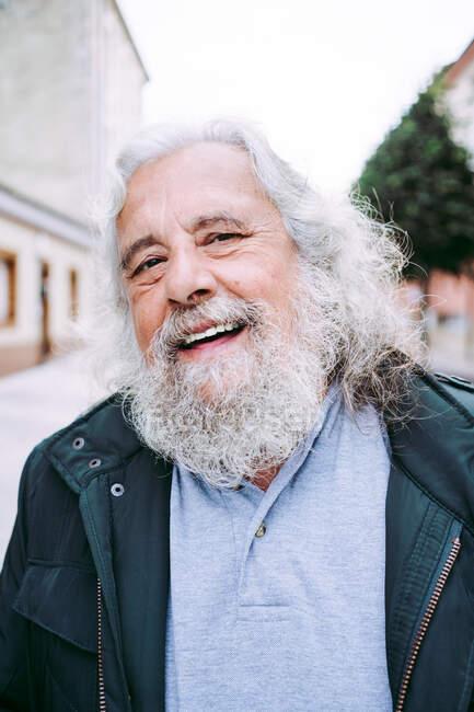 Heureux retraité homme âgé en tenue décontractée souriant à la caméra alors qu'il se tenait debout dans la rue floue de la ville le jour — Photo de stock