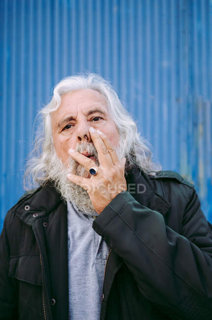 Snapshot of pensive elderly man in black jacket looking at camera and touching face while standing with shabby garage behind — Stock Photo