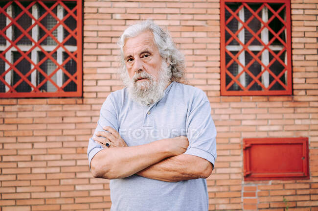 Старий бородатий чоловік у бавовняній сорочці, який дивиться на камеру, стоячи біля будинку біля горища. — стокове фото