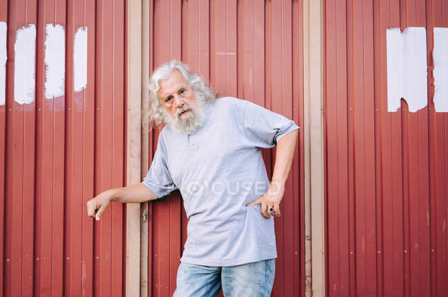 Mature aged man with grey hair in gray cotton shirt and jeans leaning on red metal wall while resting hand with signet on waist — Stock Photo
