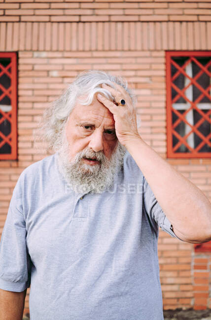 Aged bearded man in cotton tee shirt looking at camera while standing near loft building — Stock Photo