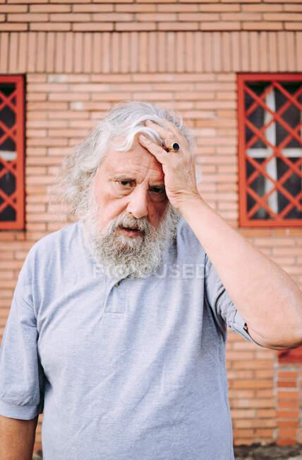 Alter bärtiger Mann im Baumwoll-T-Shirt blickt in die Kamera, während er in der Nähe eines Hochhauses steht — Stockfoto