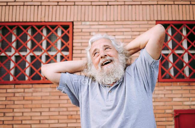 Пожилой бородатый мужчина в хлопчатобумажной футболке улыбается и смотрит в сторону, стоя с руками за головой возле лофта здания — стоковое фото