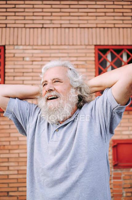 Älterer bärtiger Mann im Baumwoll-T-Shirt lächelt und schaut weg, während er mit den Händen hinter dem Kopf in der Nähe des Loftgebäudes steht — Stockfoto