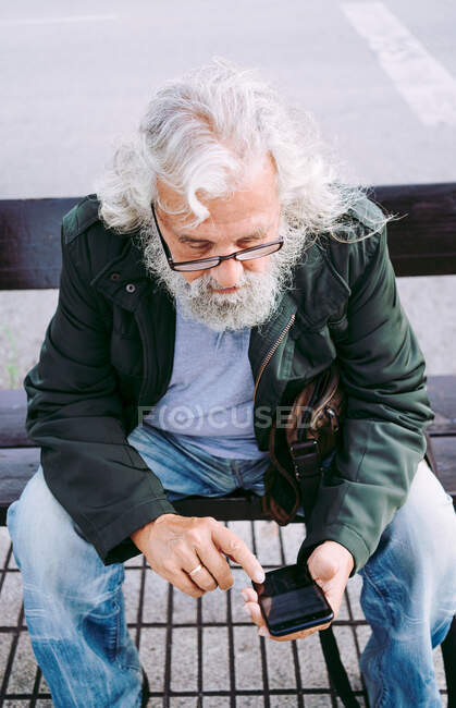 From above concentrated grey bearded man in casual clothes wearing eyeglasses and messaging on mobile phone while resting on street bench — Stock Photo