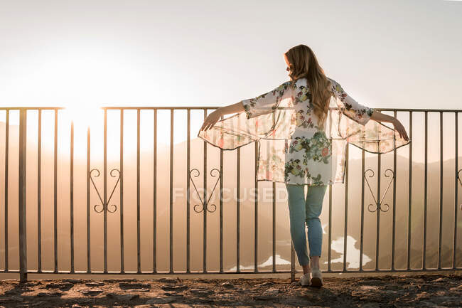 Back view of female tourist in casual clothes standing near metal fence and admiring sundown view during walk on summer day — Stock Photo