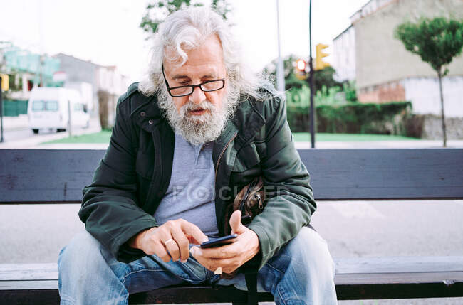 Concentrated grey bearded man in casual clothes wearing eyeglasses and messaging on mobile phone while resting on street bench — Stock Photo
