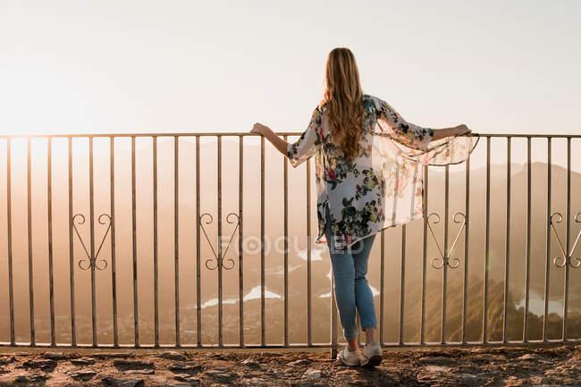 Vue arrière du touriste féminin en vêtements décontractés debout près d'une clôture métallique et admirant la vue au coucher du soleil pendant la marche le jour de l'été — Photo de stock