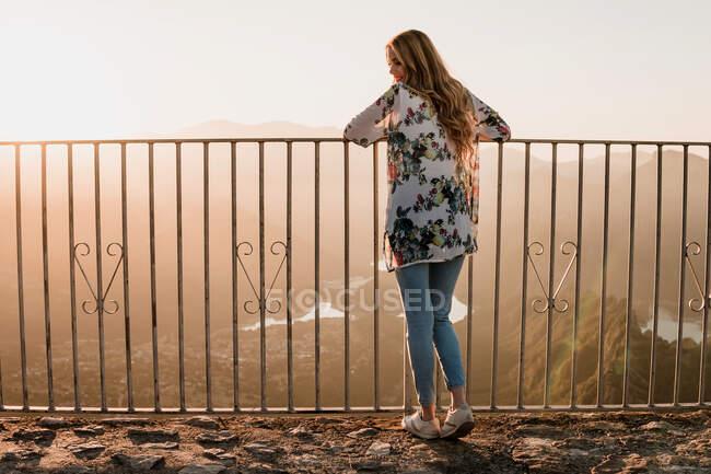 Vista trasera de la turista femenina en ropa casual de pie cerca de la valla de metal y admirando la vista del atardecer durante el paseo en el día de verano - foto de stock