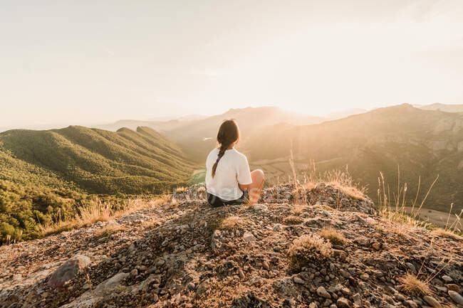 Back view of anonymous female tourist in casual clothes enjoying picturesque landscape while sitting on stony ground on sunny day in summer — Stock Photo