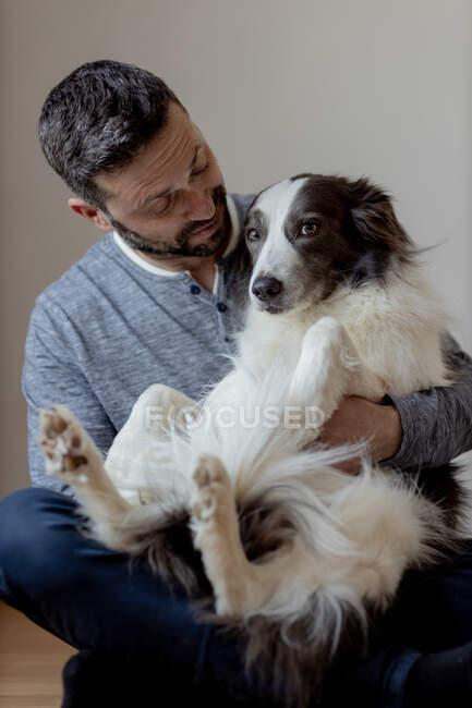 Мужчина в повседневной одежде обнимает и целует любимую собаку Пограничной Колли, сидя в позе лотоса на деревянном полу. — стоковое фото