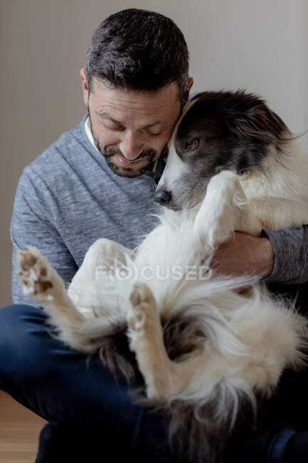 Man in casual outfit giving hug and kiss to beloved Border Collie dog while sitting in lotus position on wooden floor — Stock Photo