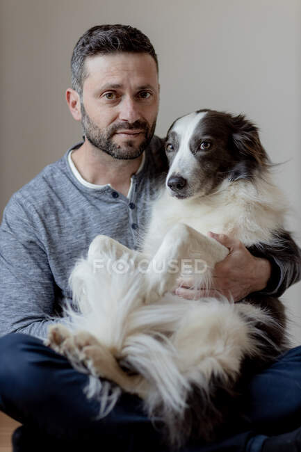 Man in casual outfit giving hug and kiss to beloved Border Collie dog while sitting in lotus position on wooden floor looking at camera — Stock Photo
