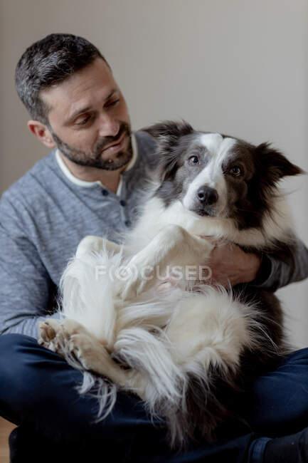 Mann in lässigem Outfit umarmt und küsst geliebten Border Collie Hund, während er in Lotusposition auf Holzboden sitzt — Stockfoto