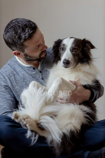 Uomo in abito casual dare abbraccio e bacio all'amato cane Border Collie mentre seduto in posizione loto sul pavimento in legno — Foto stock