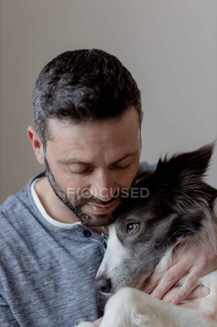 Homem de roupa casual dando abraço e beijo ao amado cão Border Collie em casa — Fotografia de Stock