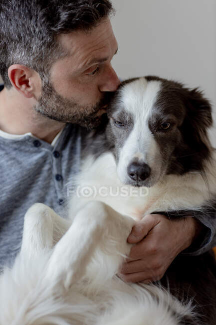 Man in casual outfit giving hug and kiss to beloved Border Collie dog at home — Stock Photo