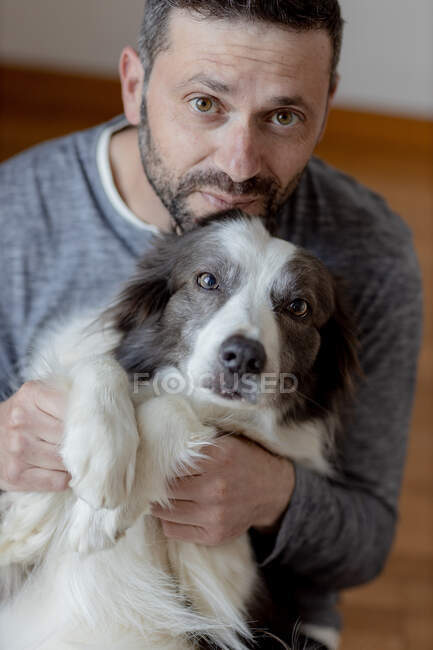 Man in casual outfit giving hug and kiss to beloved Border Collie dog while sitting in on the floor at home looking at camera — Stock Photo